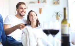 Unga älska par på tv och att skratta för soffa hemmastadd hållande ögonen på och att dricka ett exponeringsglas av rött vin arkivfoton