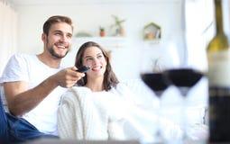 Unga älska par på tv och att skratta för soffa hemmastadd hållande ögonen på och att dricka ett exponeringsglas av rött vin royaltyfria foton