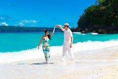 Unga älska par som har gyckel i den tropiska stranden Arkivfoton
