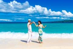 Unga älska par som har gyckel i den tropiska stranden Royaltyfria Foton