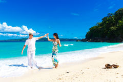 Unga älska par som har gyckel i den tropiska stranden Royaltyfria Bilder