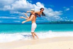 Unga älska par som har gyckel i den tropiska stranden Royaltyfri Foto