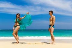 Unga älska par som har gyckel på den tropiska stranden Sommarvacatio Arkivbilder