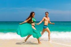 Unga älska par som har gyckel på den tropiska stranden Sommarvacatio Royaltyfri Fotografi