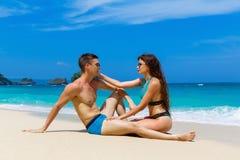 Unga älska par som har gyckel på den tropiska stranden Sommarvacatio Arkivbild