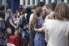 Unga älska par som omfamnar och kysser på rusningstiden nära den tunnelbanaCovent trädgården Royaltyfria Foton