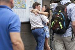 Unga älska par som omfamnar och kysser på rusningstiden nära den tunnelbanaCovent trädgården Arkivbilder