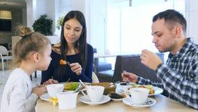Unga älskvärda föräldrar som matar deras blonda dottergrönsaksallad i kafé Arkivfoton