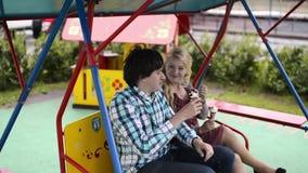 Unga älskvärda par på gungor som äter iscreamand, har gyckel stock video