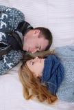 Unga älskvärda par som ligger i en säng, lyckligt leende som till varandra ser Royaltyfri Bild