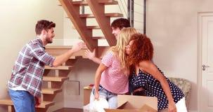 Unga älskvärda par som packar upp askar, medan besöka vid vänner lager videofilmer