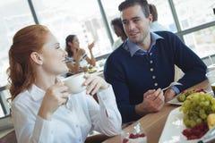 Unga affärskollegor som i regeringsställning talar på frukosttabellen Fotografering för Bildbyråer