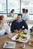 Unga affärskollegor som talar på frukosttabellen Royaltyfria Foton