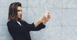 Unga affärskvinnor för stående i svart dräkt genom att använda smartphonen som isoleras på den konkreta gråa väggmodellen för bak royaltyfria bilder