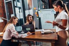 Unga affärskvinnor på presentationen Kvinnlig kollega som visar ett diagram som förklarar ny affärsstrategi fotografering för bildbyråer