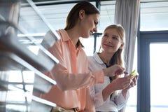 Unga affärskvinnor som i regeringsställning använder mobiltelefonen Arkivfoto