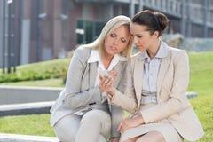 Unga affärskvinnor som tillsammans använder mobiltelefonen, medan sitta mot kontorsbyggnad Arkivbilder