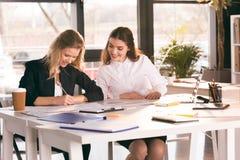 Unga affärskvinnor som tillsammans arbetar på tabellen med bärbara datorn Arkivbilder