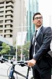 Unga affärsmän med en cykel Arkivbild