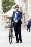 Unga affärsmän med en cykel Arkivbilder