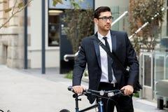 Unga affärsmän med en cykel Fotografering för Bildbyråer