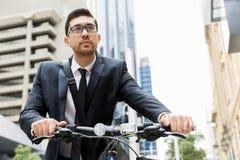 Unga affärsmän med en cykel Royaltyfria Bilder