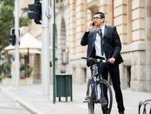 Unga affärsmän med en cykel Arkivfoto