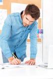 Unga affärsmandanandeanmärkningar, medan stå på kontorsskrivbordet arkivfoto