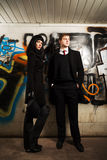 Unga affärspar på grafittiväggundergren Arkivfoto