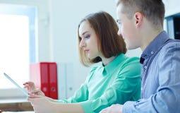 Unga affärspartners som ser data på minnestavlaskärmen i företags kontor affär som pekar skärmkvinnan royaltyfri fotografi