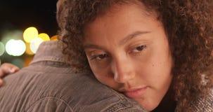 Unga afrikansk amerikanpar som omfamnar sig i staden royaltyfri foto