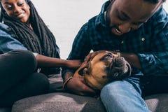 unga afrikansk amerikanpar som sitter på soffan och trycker på fransman royaltyfri fotografi
