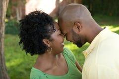 Unga afrikansk amerikanpar som skrattar och kramar Royaltyfria Foton