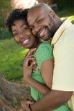 Unga afrikansk amerikanpar som skrattar och kramar Arkivbilder