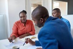 Unga afrikanska affärskollegor som diskuterar skrivbordsarbete i ett kontor fotografering för bildbyråer