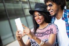 Unga afrikanska par poserar f?r ferieselfie i stad royaltyfri fotografi