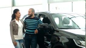 Unga afrikanska par som väljer en bil på bilsalongen lager videofilmer