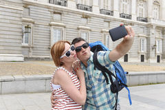 Unga amerikanska par som tycker om Spanien ferie, snubblar ta selfiefotoet självståenden med mobiltelefonen Arkivbild