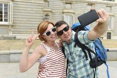 Unga amerikanska par som tycker om Spanien ferie, snubblar ta selfiefotoet självståenden med mobiltelefonen Royaltyfri Bild