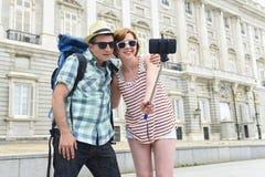 Unga amerikanska par som tycker om Spanien ferie, snubblar ta selfiefotoet självståenden med mobiltelefonen Arkivfoton