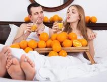 Unga angenäma par med mogna apelsiner och nytt fruktsaft Royaltyfri Bild