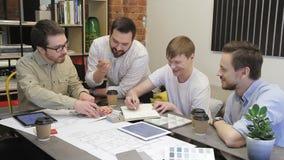 Unga anställda arbetar sammanträde på tabellen i regeringsställning av företaget inomhus lager videofilmer