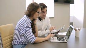 Unga anställda som arbetar i modernt kontor genom att använda bärbara datorn och minnestavlan arkivfilmer