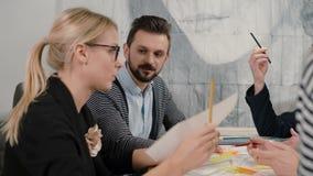 Unga arkitekter för idérikt små och medelstora företaglag som möter i det startup kontoret som diskuterar aktivt nya idéer stock video