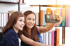 Unga asiatiska affärskvinnor för lycka som tillsammans tar en bild eller en selfie i regeringsställning med solskeneffekt arkivbilder