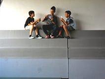 Unga asiatiska barn som spelar kort arkivbild
