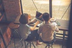 Unga asiatiska freelancers som arbetar på bärbara datorn royaltyfri foto