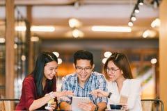 Unga asiatiska högskolestudenter eller coworkers som tillsammans använder den digitala minnestavlan på coffee shop, olik grupp Ti royaltyfri bild