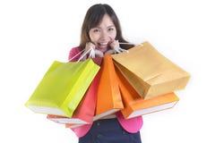 Unga asiatiska kvinnor för shopping som rymmer shoppingpåsar på det vita studiobackgroundSale och befordranbegreppet Arkivfoton