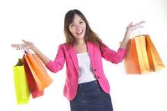 Unga asiatiska kvinnor för shopping som rymmer shoppingpåsar på det vita studiobackgroundSale och befordranbegreppet Royaltyfri Fotografi